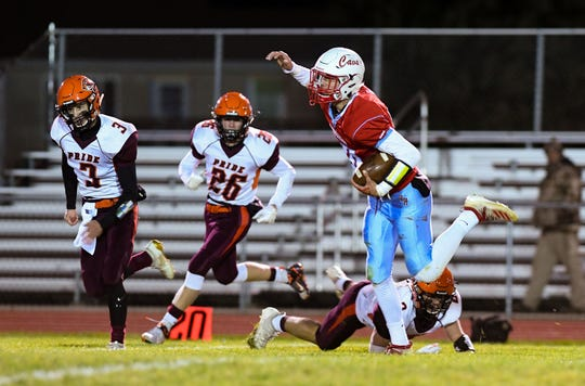 Joshua Crownover of Bon Homme stumbles past members of the Canistota/Freeman defense during their game on Friday, October 11, in Tyndall.