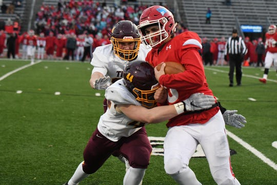 Lincoln quarterback Tommy Thompson gets tackled by Harrisburg defender Ayden Viox during a Class 11 AAA matchup Friday night at Howard Wood Field.