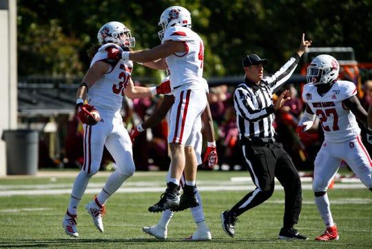 The University of South Dakota's Jack Cochrane (39) and Elijah Reed (4) celebrate after Cochrane made an interception on Missouri State at Plaster Field on Saturday, Oct. 12, 2019.