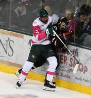 St. Cloud State sophomore Sam Hentges takes a hit against the boards from Bemidji State's Will Zmolek in Friday's contest.