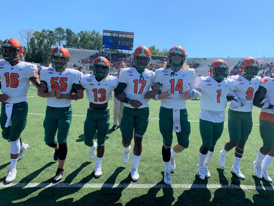 FAMU players lock arms in prep for the MEAC clash at South Carolina State on Saturday, Oct. 12, 2019.