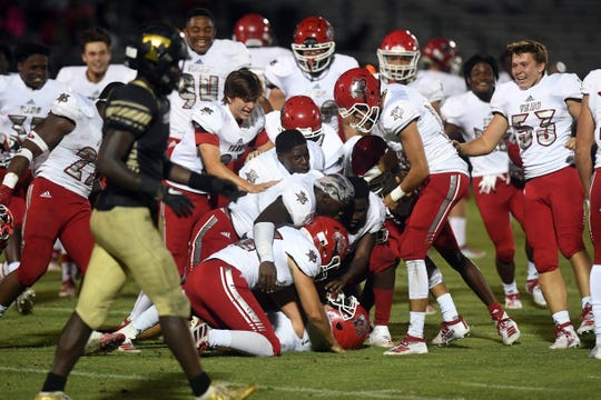 Vero Beach High School kicker Henry Morgan is tackled by the rest of the Fighting Indians on Friday, Oct. 11, 2019, after Morgan put the ball through the uprights to give Vero Beach a 31-30 overtime victory over Treasure Coast at the South County Regional Stadium in Port St. Lucie.