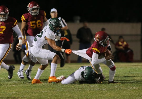 Pacifica High's Caleb McCullough pulls down Oxnard quarterback Jaden Jones by his jersey during the second quarter of Friday night's game. Oxnard won, 36-27.