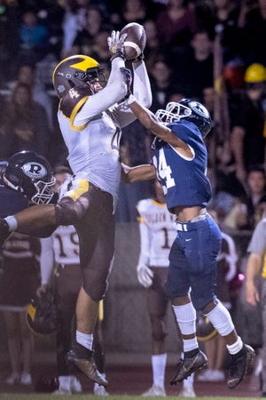Golden West's Lonnie Wessel pulls down a pass under pressure formRedwood's Mitchell Wilson in a West Yosemite League high school football game on Friday, October 11, 2019.