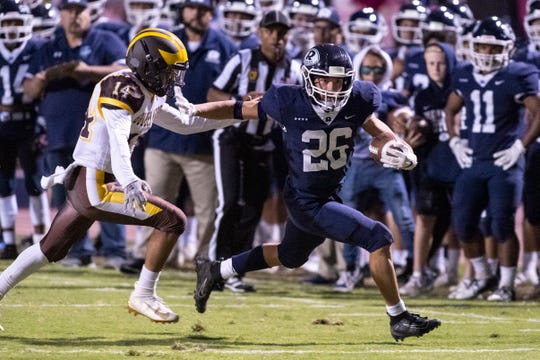 Redwood's Caden Shafer runs away from Golden West's Samuel Cervantes in a West Yosemite League high school football game on Friday, October 11, 2019.