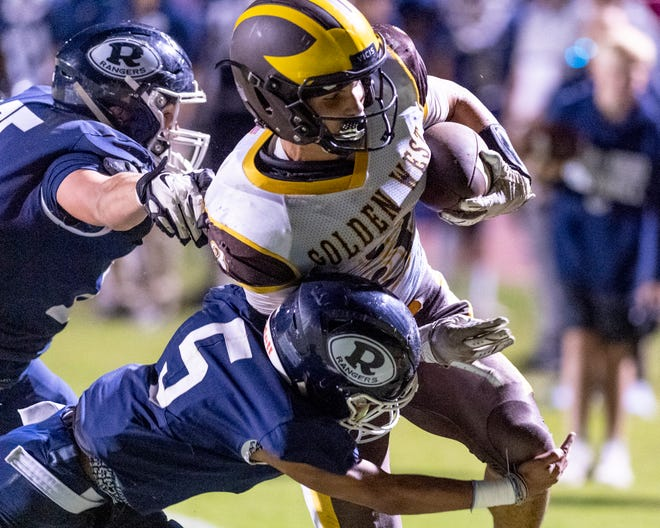 Golden West's Michael Wessel gets around Redwood's Quinton Johnson to score in a West Yosemite League high school football game on Friday, October 11, 2019.