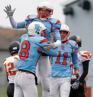 Newman Catholic's Thomas Bates (2) celebrates with Joe Stephan (8) after Stephan's second-quarter touchdown reception against Phillips during a game last month in Wausau.