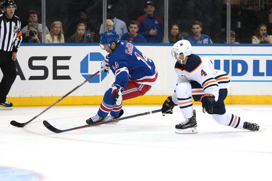 Oct 12, 2019; New York, NY, USA; New York Rangers center Greg McKegg (14) carries the puck as Edmonton Oilers defenseman Kris Russell (4) defends during the second period at Madison Square Garden. Mandatory Credit: Vincent Carchietta-USA TODAY Sports