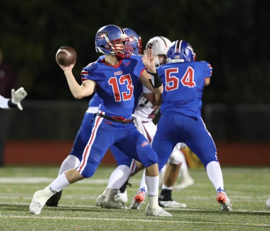 Carmel's Andrew Nunez (13) looks down field for a receiver during their 38-7 win over Scarsdale at Carmel High School on Friday, October 11, 2019.