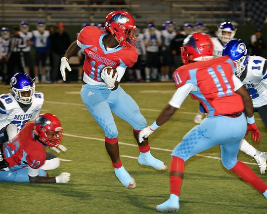 Hirschi's KD Dorsey (10) spins as he runs the ball against Decatur Friday night at Memorial Stadium.