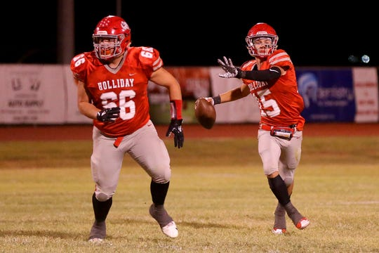 Holliday's Quarterback prepares to throw the pass under the protection of team mate Ryan Hipol Friday night in Holliday.
