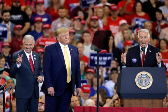 President Donald Trump introduces Louisiana Republican gubernatorial candidates Eddie Rispone, left, and Ralph Abraham, during a campaign rally in Lake Charles, La. The two are running against incumbent Democrat Gov. John Bel Edwards.