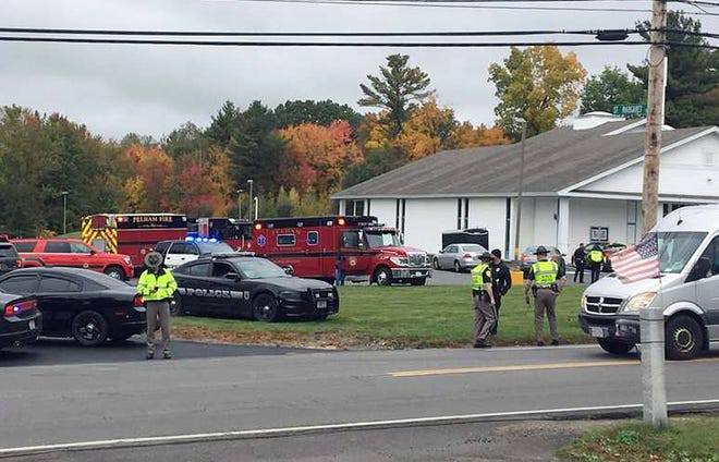 In this photo provided by WMUR-TV, police stand outside the New England Pentecostal Church on Saturday, Oct. 12, 2019, in Pelham, N.H.