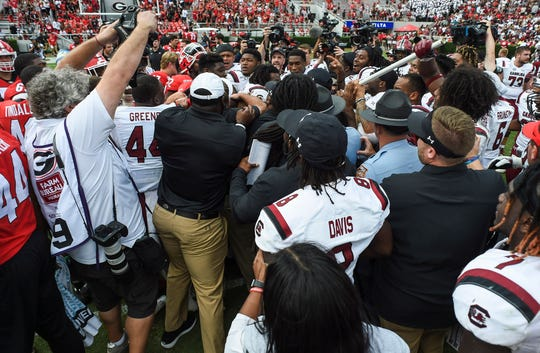 South Carolina and Georgia players scuffle on the field after the Gamecocks defeated the Bulldogs in overtime at Sanford Stadium.