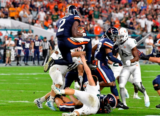 Virginia Cavaliers wide receiver Joe Reed (2) leaps over Miami Hurricanes kicker Bubba Baxa (21) during a kickoff in the second half at Hard Rock Stadium.
