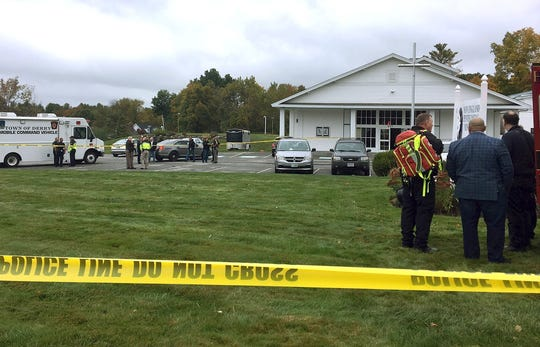 In this photo provided by WMUR-TV, police stand outside the New England Pentecostal Church after reports of a shooting on Saturday, Oct. 12, 2019, in Pelham, N.H. WMUR-TV reports that Hillsborough County Attorney Michael Conlon said a suspect is in custody.