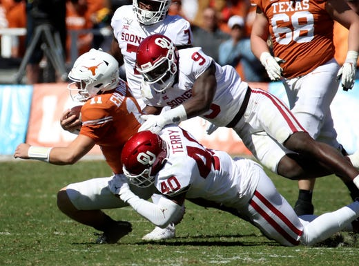 Oklahoma linebackers Jon-Michael Terry (40) and Kenneth Murray tackle Texas quarterback Sam Ehlinger during the first half at the Cotton Bowl.