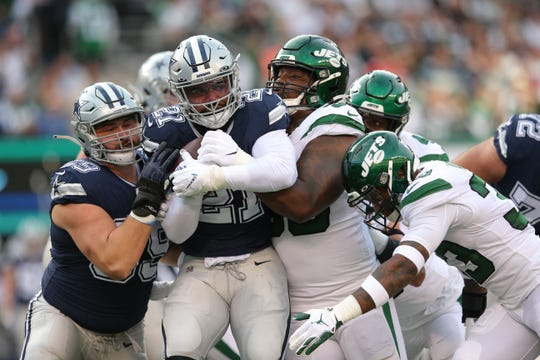 Dallas Cowboys running back Ezekiel Elliott (21) is stopped by New York Jets defensive tackle Steve McLendon (99) and safety Jamal Adams (33) during the second quarter at MetLife Stadium.