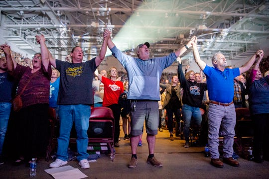 People in the front row join hands in prayer and song as Jeremy Camp performs for the crowd during the final stop of Franklin Graham's Decision America Tar Heel State Tour at the U.S. Cellular Center on Oct. 13, 2019.