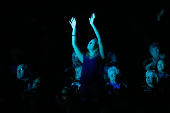 Candice Howard, of Hendersonville, lifts her arms as Jeremy Camp performs for the crowd during the final stop of Franklin Graham's Decision America Tar Heel State Tour at the U.S. Cellular Center on Oct. 13, 2019.