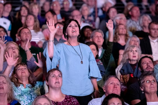Tracey Dykes, of Mars Hill, lifts her hand in praise as Jeremy Camp performs for the crowd during the final stop of Franklin Graham's Decision America Tar Heel State Tour at the U.S. Cellular Center on Oct. 13, 2019.