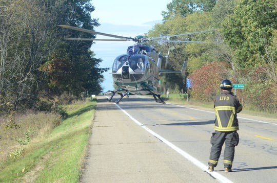 A leroy Township firefighter stands by as the AirCare medical helicopter leaves with one patient after a crash south of Battle Creek on Sunday.