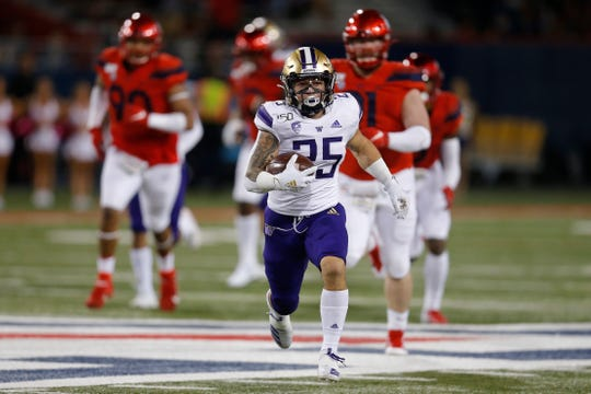 Washington running back Sean McGrew (25) runs for a first down against Arizona on Saturday, Oct. 12, 2019, in Tucson, Ariz.