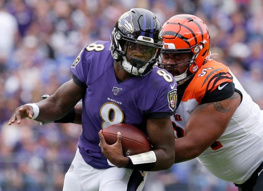 Baltimore Ravens quarterback Lamar Jackson (8) is wrapped up by Cincinnati Bengals defensive tackle Josh Tupou (91) in the first quarter of the NFL Week 6 game between the Baltimore Ravens and the Cincinnati Bengals at M&T Bank Stadium in Baltimore on Sunday, Oct. 13, 2019.
