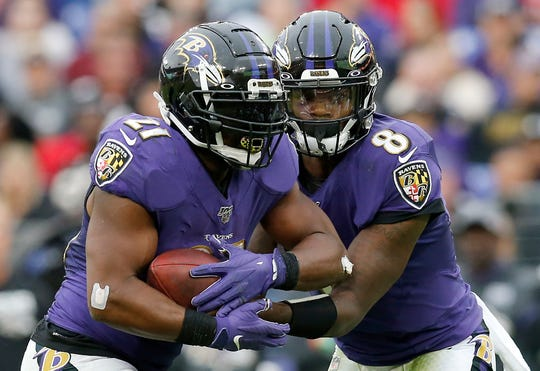 Baltimore Ravens quarterback Lamar Jackson (8) hands off to running back Mark Ingram (21) in the fourth quarter of the NFL Week 6 game between the Baltimore Ravens and the Cincinnati Bengals at M&T Bank Stadium in Baltimore on Sunday, Oct. 13, 2019. The Bengals remained winless with a 23-17 loss to the Ravens.