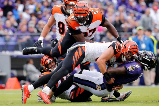 Baltimore Ravens quarterback Lamar Jackson (8) is stopped short of the goal line by Cincinnati Bengals outside linebacker Nick Vigil (59) on a run in the first quarter of the NFL Week 6 game between the Baltimore Ravens and the Cincinnati Bengals at M&T Bank Stadium in Baltimore on Sunday, Oct. 13, 2019.
