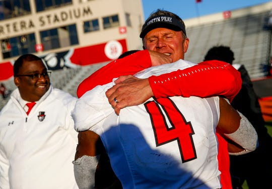 Austin Peay head coach Mark Hudspeth embraces Prince Momodu (4) after winning an OVC game against the Southeast Missouri Redhawks on Saturday.