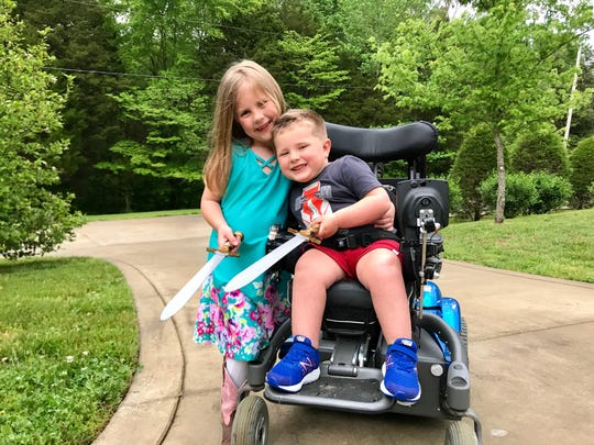 Oliver Schaper, a Middle Tennessee boy diagnosed with SMA several years ago, smiles while playing swords with his big sister Elliott, a simple childhood joy made possible by groundbreaking SMA treatments that have now led state health officials to add SMA to newborn screenings.