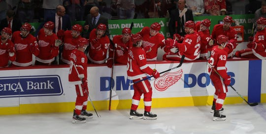 Left to right: Justin Abdelkader, Jacob de la Rose and Darren Helm skate past the Wings' bench to celebrate a goal against the Leafs during the third period.