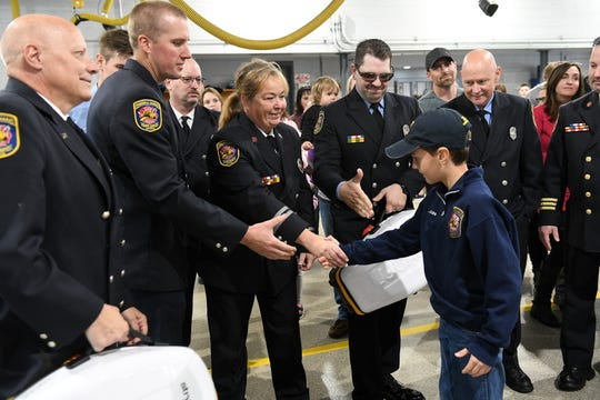 Lucas Vetter of Rose Township shakes hands with Capt. Annie Appleyard and other members of the Howell Fire Department. Appleyard said the device was used to save a life and she earned her Chain of Life certificate during the first week that her station had one of the LUCAS systems.