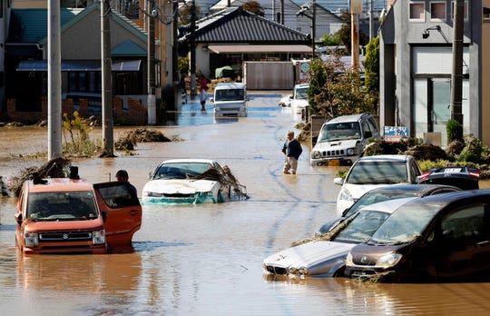 Vehicles are seen in mud water as Typhoon Hagibis hit the city in Sano, Tochigi prefecture, Sunday, Oct. 13, 2019.