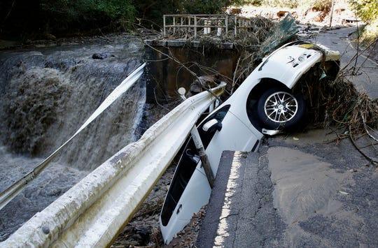 A vehicle falls off collapsed road in the typhoon-hit Kakuda city, Miyagi prefecture, northern Japan,  Sunday, Oct. 13, 2019.