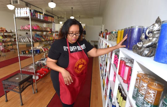 Team leader Kay (no last name given) straightens out merchandise on the shelves at Discount Candles in Eastern Market.  The business recently moved to 1448 Gratiot after its previous building was sold and rent rates spiked.