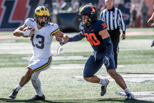Michigan's Tru Wilson, who had a fumble Saturday, runs past Illinois' Sydney Brown.