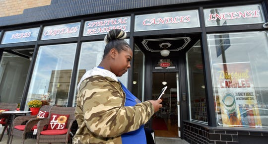 Samantha Thomas of Detroit checks her cell phone in front of Discount Candles in Eastern Market. The business recently moved to 1448 Gratiot after its previous building was sold and rent rates spiked.