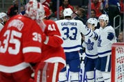 Toronto Maple Leafs center Nicholas Shore, right, celebrates with center Frederik Gauthier (33) and left wing Dmytro Timashov, center, after scoring against the Detroit Red Wings during the first period on Saturday.