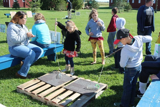 "Local children enjoy an old fashion vintage game at the ""Farm Days"" event at Creek Bend Farm on Saturday."