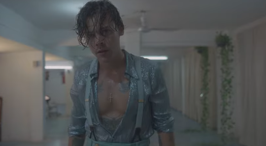 "Harry Styles wearing a chest-baring, shimmery light blue outfit in the ""Lights Up"" music video."