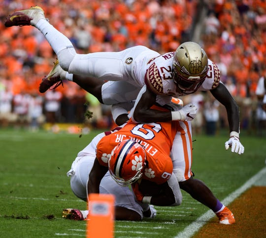 Clemson running back Travis Etienne (9) is taken down by Florida State defensive back Akeem Dent (27) and defensive back Hamsah Nasirildeen (23) during their game at Memorial Stadium Saturday, October 12, 2019.