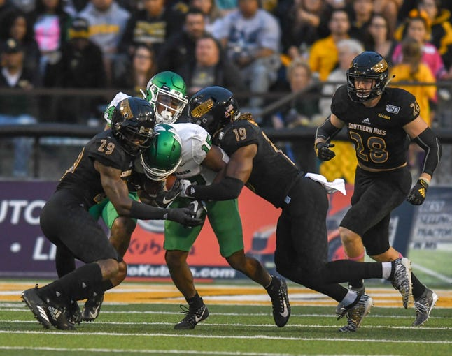 Southern Miss defensive backs Ernest Gunn and Ky'el Hemby tackle North Texas running back Tre Siggers during the first half Saturday, Oct. 12, 2019.