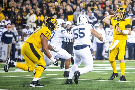 Iowa quarterback Nate Stanley (4) throws a pass while getting pressure from Penn State's P.J. Mustipher (97) and Antonio Shelton (55) during a NCAA Big Ten Conference football game between the Iowa Hawkeyes and Penn State, Saturday, Oct., 12, 2019, at Kinnick Stadium in Iowa City, Iowa.