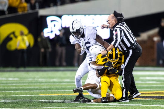 Iowa running back Tyler Goodson (15) collides with umpire Jeff Carr while attempting to catch a pass as Penn State's Tariq Castro-Fields (5) and Cam Brown (6) defend during a NCAA Big Ten Conference football game between the Iowa Hawkeyes and Penn State, Saturday, Oct., 12, 2019, at Kinnick Stadium in Iowa City, Iowa.