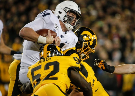 A host of Iowa defenders tackle Penn State quarterback Sean Clifford in the third quarter on Saturday, Oct. 12, 2019, at Kinnick Stadium in Iowa City.