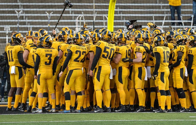 The Iowa Hawkeyes gather before the game against the Penn State Nittany Lions in their alternate uniforms at Kinnick Stadium.