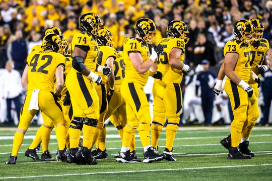 Iowa offensive linemen get set after a huddle during a NCAA Big Ten Conference football game between the Iowa Hawkeyes and Penn State, Saturday, Oct., 12, 2019, at Kinnick Stadium in Iowa City, Iowa.