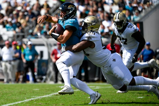 Oct 13, 2019; Jacksonville, FL, USA; Jacksonville Jaguars quarterback Gardner Minshew (15) scrambles with the ball against New Orleans Saints defensive tackle Shy Tuttle (99) during the first quarter at TIAA Bank Field. Mandatory Credit: Douglas DeFelice-USA TODAY Sports